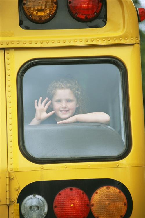 Smiling child waving through bus window